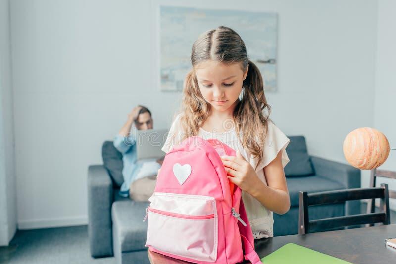 милая маленькая девочка подготавливая рюкзак стоковое фото