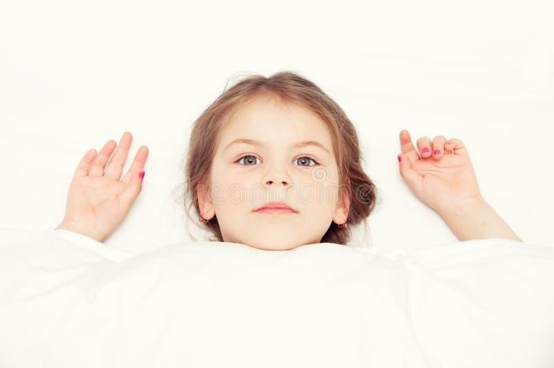 Милая маленькая девочка под одеялом в кровати в спальне Лежать дальше стоковое изображение
