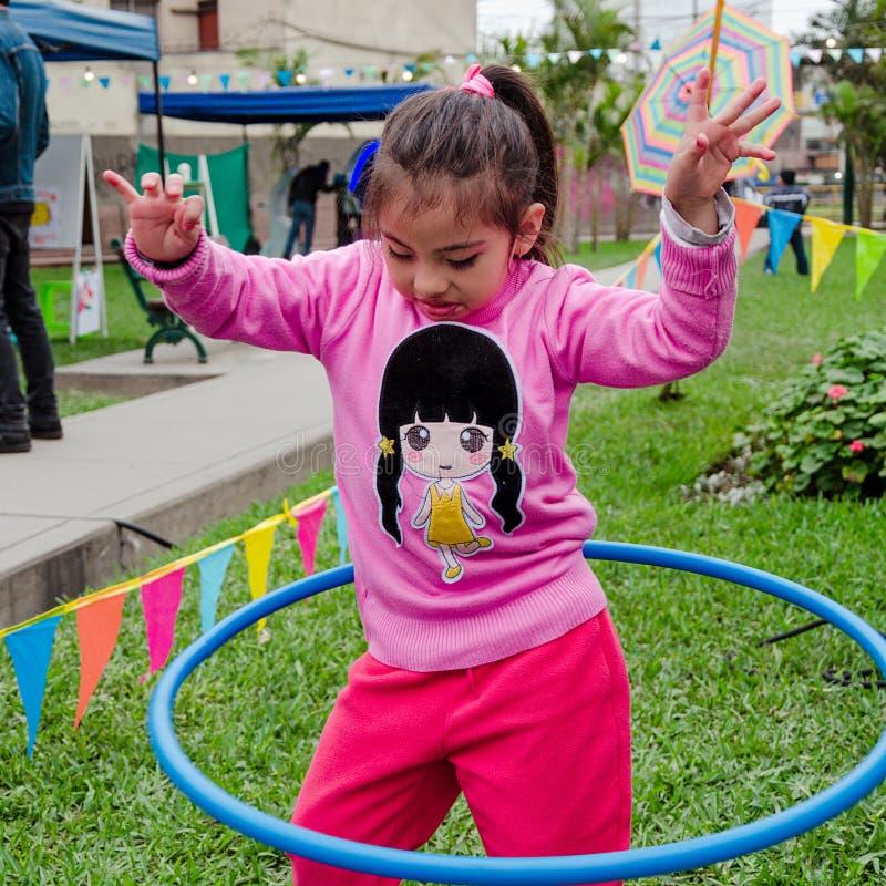 Милая маленькая девочка представляя с ее обручем hula стоковое фото