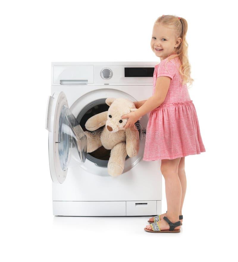 Милая маленькая девочка принимая плюшевый мишку из стиральной машины стоковая фотография