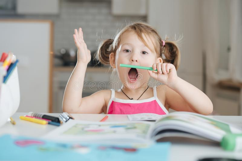 Милая маленькая девочка рисует с ручкой войлок-подсказки дома стоковое фото rf
