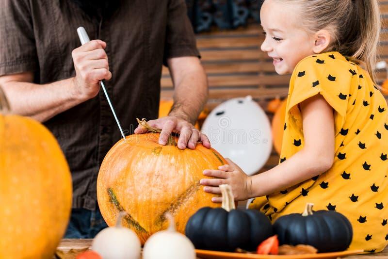 Милая маленькая девочка сидя на кухонном столе, помогая ее отцу высечь большую тыкву Образ жизни семьи хеллоуина стоковые фотографии rf