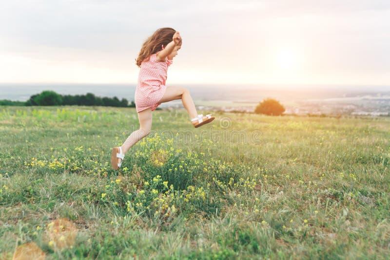 Милая маленькая девочка скача outdoors стоковое изображение rf