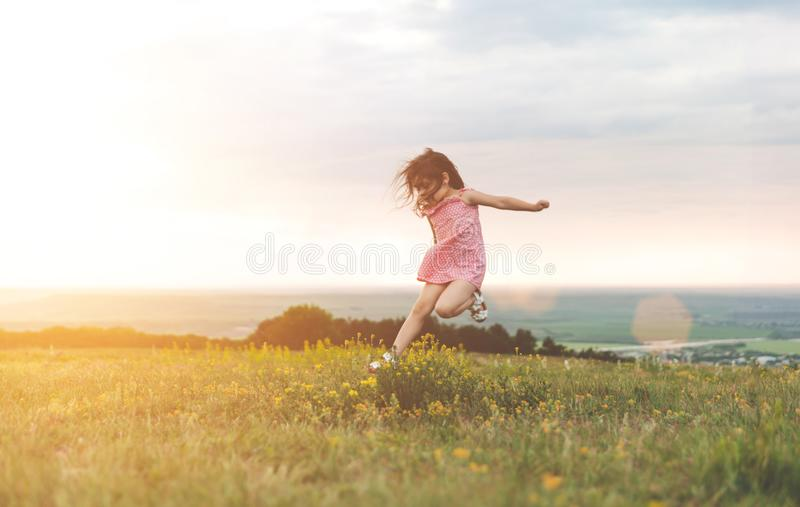 Милая маленькая девочка скача outdoors стоковое изображение