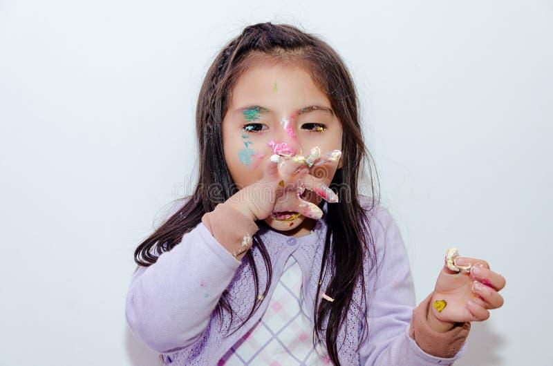 Милая маленькая девочка смазанная с тортом на ее стороне стоковые фотографии rf