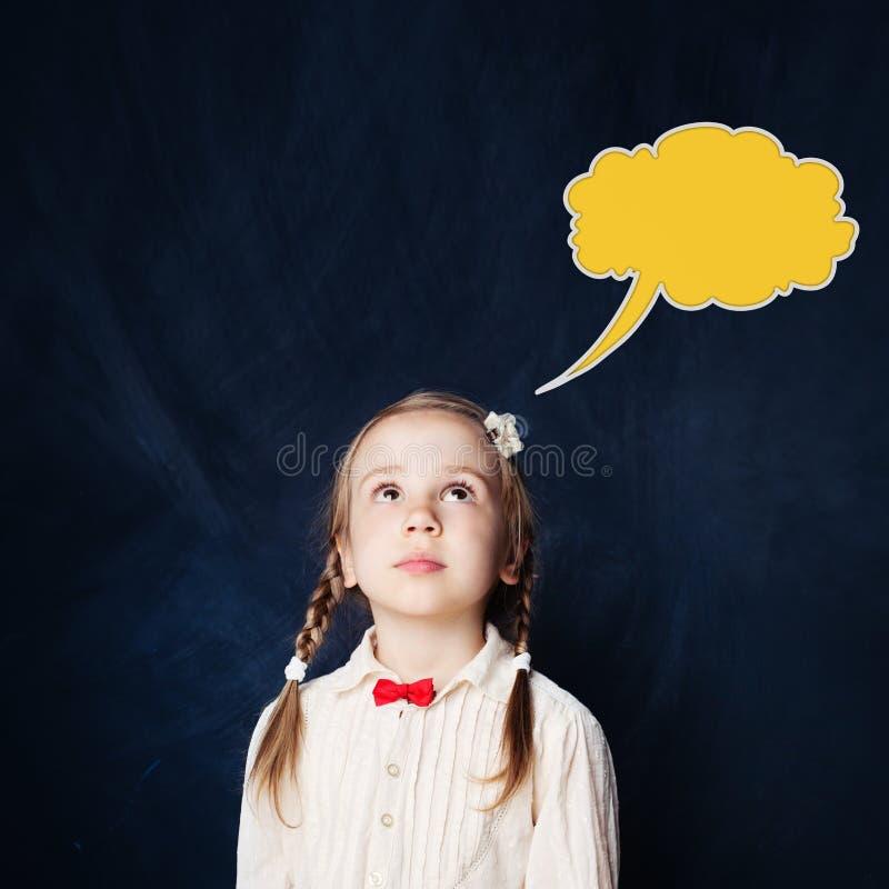 Милая маленькая девочка смотря вверх на пузыре облака речи стоковое фото rf