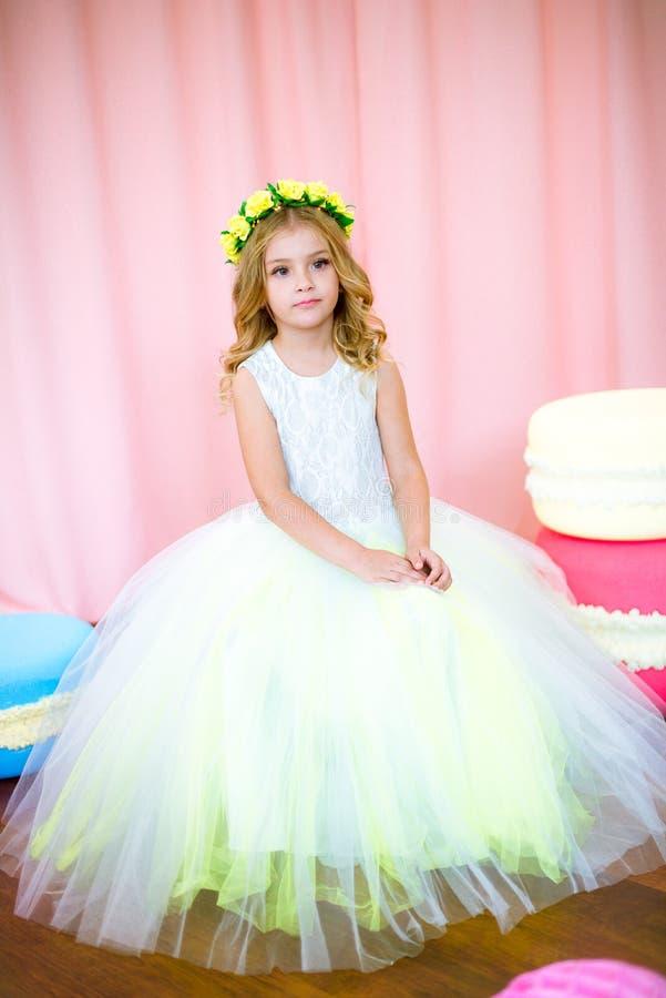 Милая маленькая девочка с белокурыми скручиваемостями в белом сочном платье с гигантскими помадками в розовой предпосылке стоковое фото