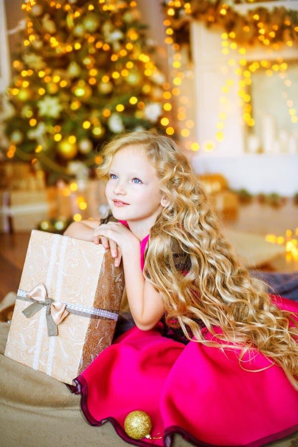 Милая маленькая девочка с курчавыми светлыми волосами дома около рождественской елки с подарками и гирляндами стоковые фотографии rf