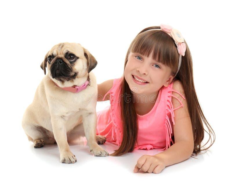 Милая маленькая девочка с собакой мопса на белой предпосылке стоковое фото