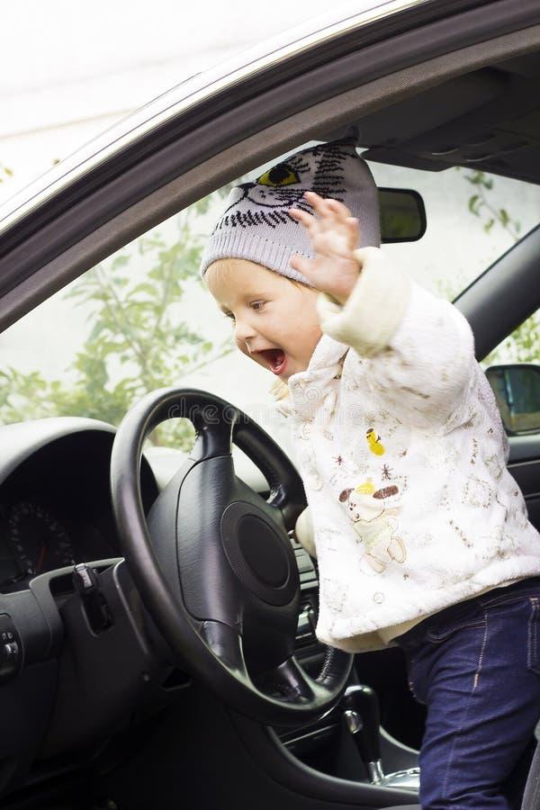 Милая маленькая девочка управляя автомобилем стоковые фото