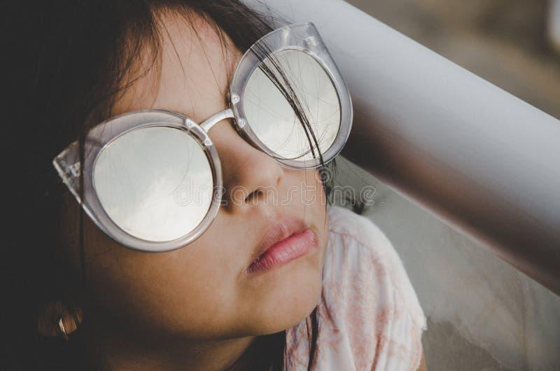 Милая маленькая девочка усмехаясь с солнечными очками стоковая фотография rf
