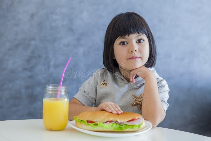 Милая маленькая девочка черных волос имея завтрак и выпивая апельсин стоковые фото