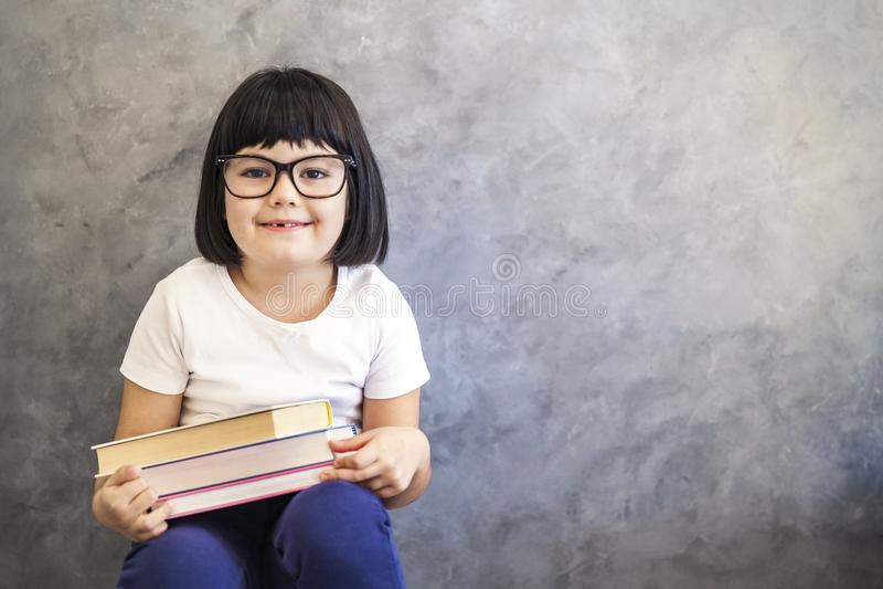 Милая маленькая девочка черных волос при стекла держа книги wa стоковое фото rf