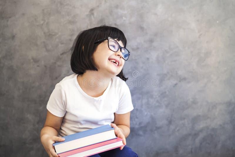 Милая маленькая девочка черных волос при стекла держа книги wa стоковые изображения