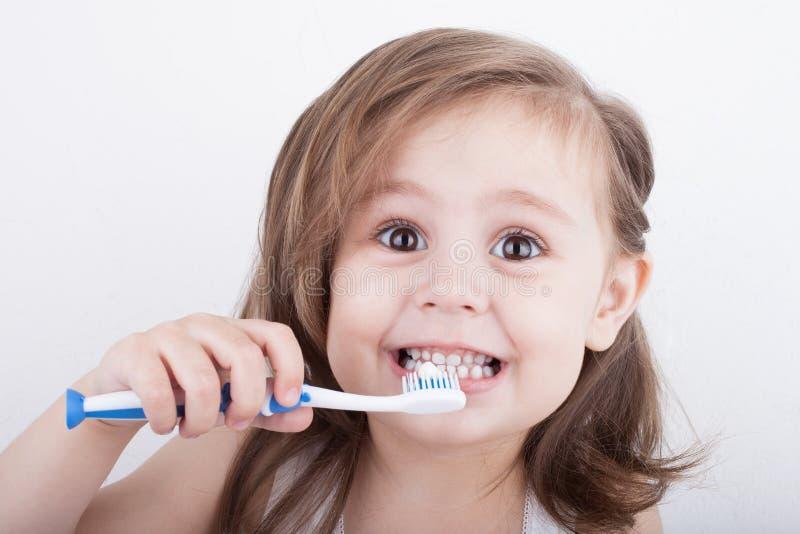 Милая маленькая девочка чистя его зубы щеткой стоковые изображения rf