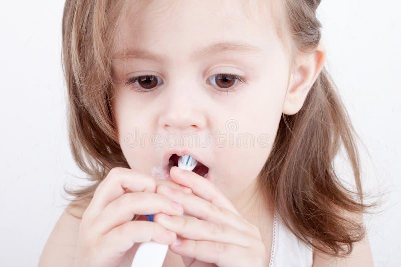 Милая маленькая девочка чистя ее зубы щеткой стоковые фото