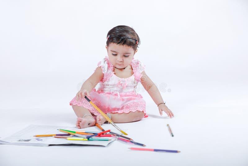 Милая маленькая индийская/азиатская девушка наслаждаясь красить с бумагой, pencle цвета и щеткой искусства стоковое фото