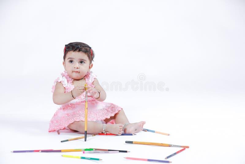 Милая маленькая индийская/азиатская девушка наслаждаясь красить с бумагой, pencle цвета и щеткой искусства стоковое изображение