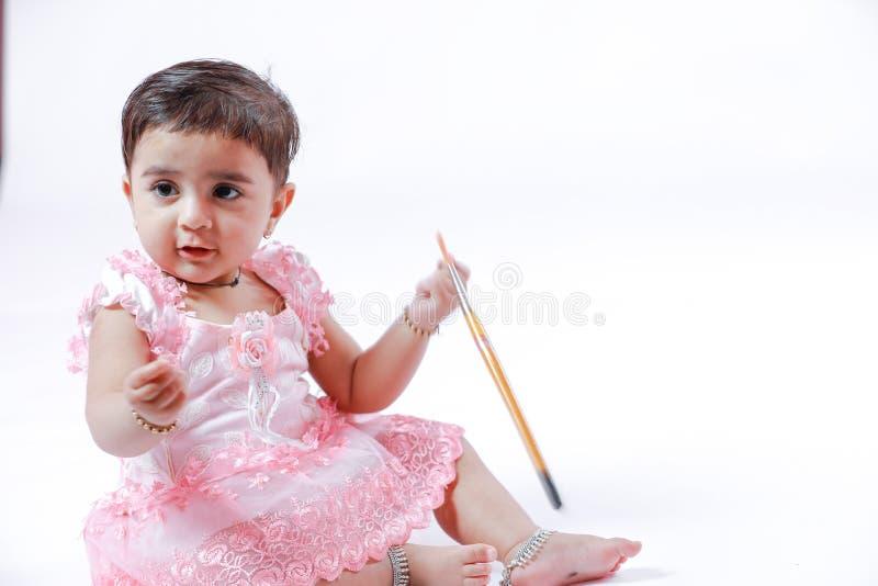 Милая маленькая индийская/азиатская девушка наслаждаясь красить с бумагой, pencle цвета и щеткой искусства стоковая фотография