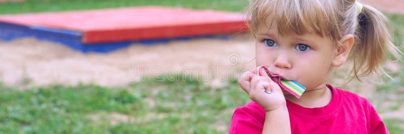 Милая маленькая кавказская девушка наслаждается съесть жевательную резинку на спортивной площадке детского сада на красивый летни стоковая фотография rf