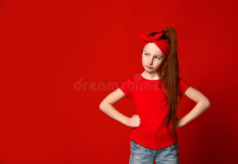 Милая маленькая рыжеволосая девушка быть в дурном настроении и хмурясь пока держащ руки на разочарованной талии, обиденной и стоковые фотографии rf