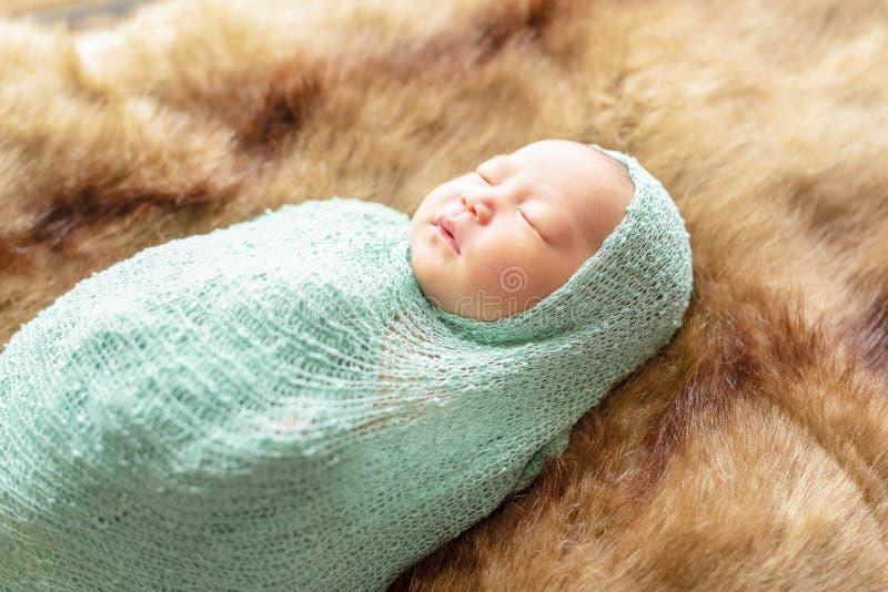 Милая маленькая newborn девушка лежа на коричневый меховой носить одеяла стоковая фотография