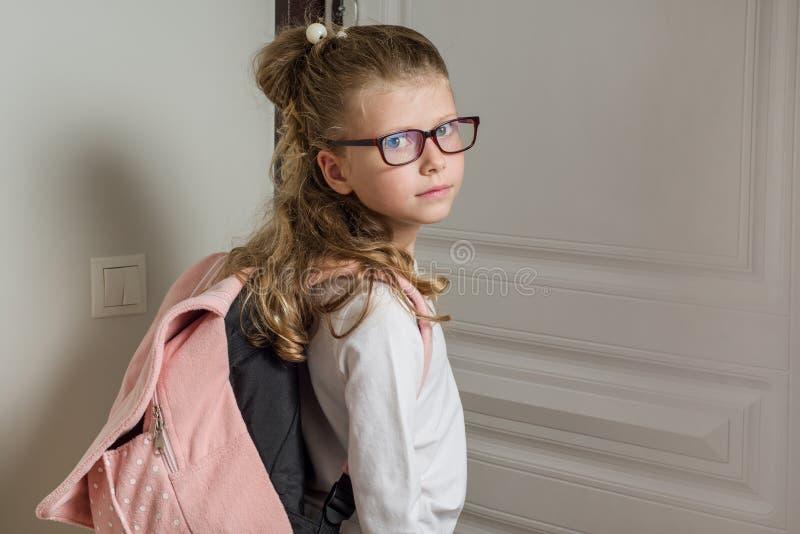 Милая младшая школьница при светлые волосы идя к школе, стоя стоковые фотографии rf