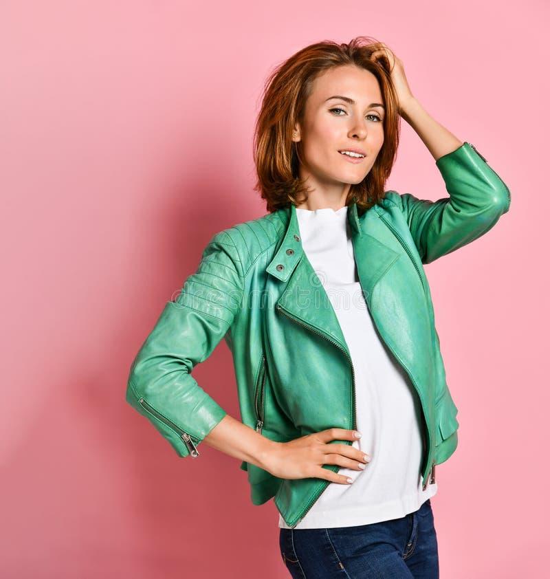 Милая модель в зеленой куртке полагаясь против ладони, стоя над розовой стеной с равнодушным раздражанным выражением стоковые фото