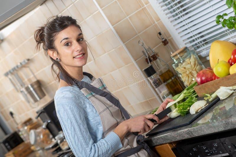Милая молодая женщина брюнета варя в кухне стоковая фотография rf