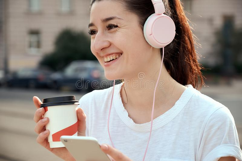 Милая молодая женщина выпивая takeout кофейную чашку, используя умный телефон, слушая к музыке в наушниках outdoors стоковые фотографии rf
