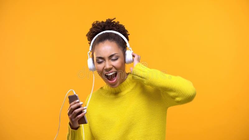 Милая молодая женщина в белых наушниках наслаждаясь звуком музыки на желтой предпосылке стоковые фотографии rf