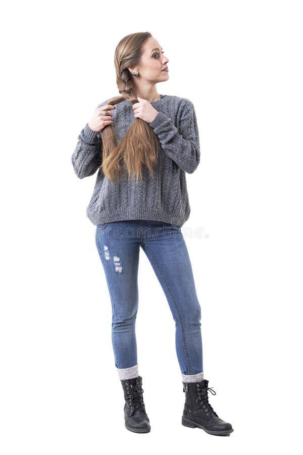 Милая молодая женщина в связанном прыгуне создавая оплетки волос смотря прочь на зеркале стоковые фотографии rf