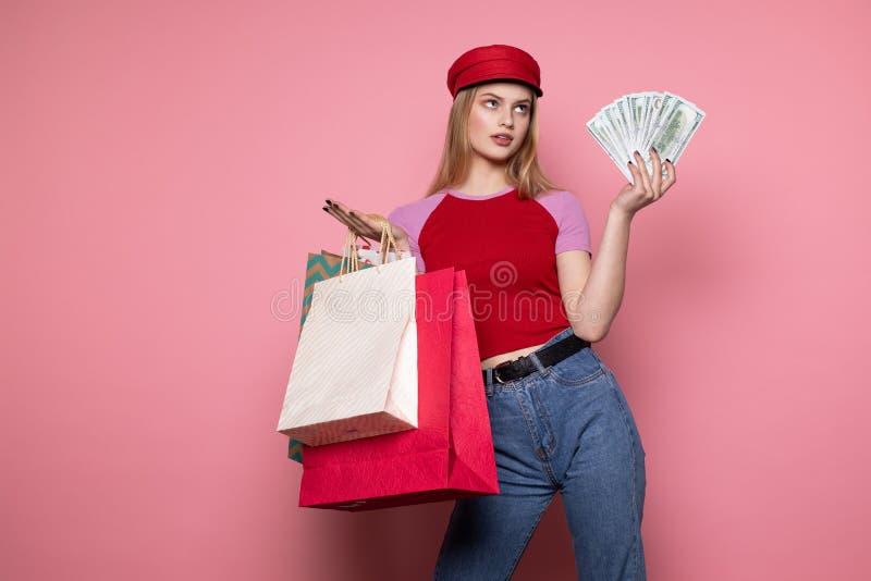 Милая молодая женщина в случайных одеждах и ультрамодной красной шляпе с красочными хозяйственными сумками и деньгами в руках стоковые фото
