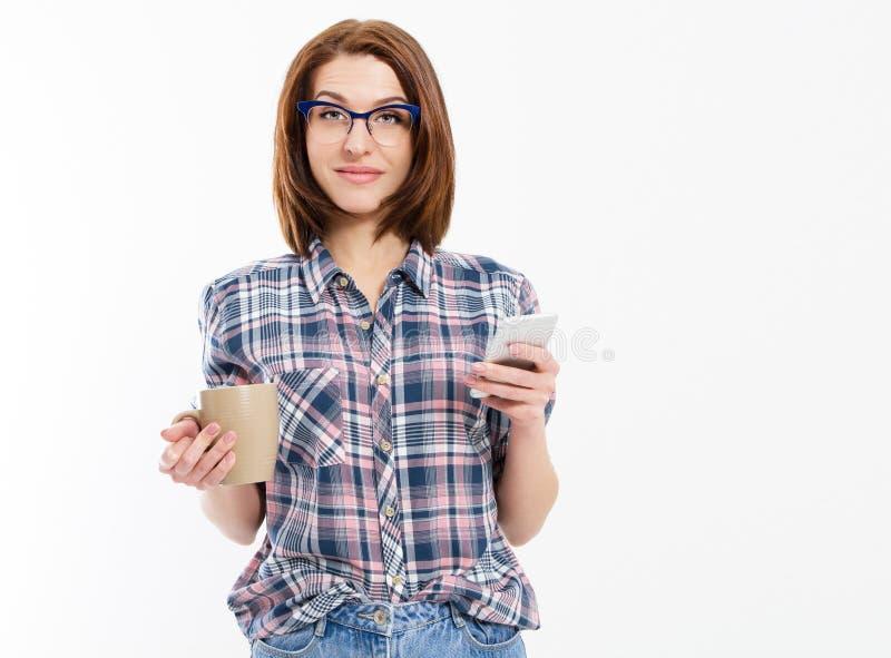 Милая молодая женщина держа умный телефон, используя прибор, нося стильные стекла, усмехаться, держа кружку, изолированную на бел стоковое фото rf