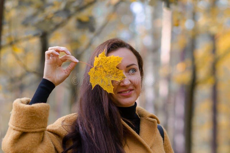 Милая молодая женщина идя в падение листьев парка осени ослабляет моду отдыха современную стоковые фотографии rf