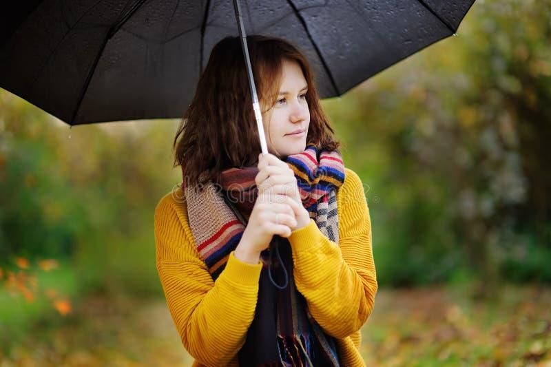 Милая молодая женщина идя на ненастную пасмурную погоду осени стоковые изображения rf