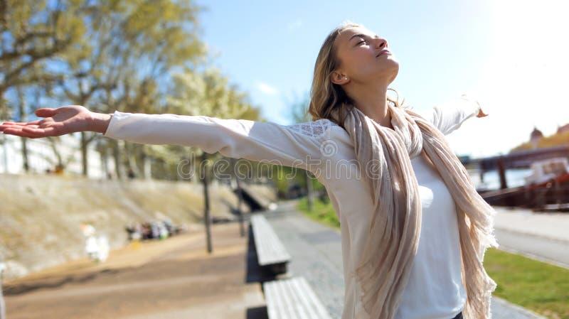Милая молодая женщина наслаждаясь весной с оружиями поднятыми к небу на улице стоковое изображение rf