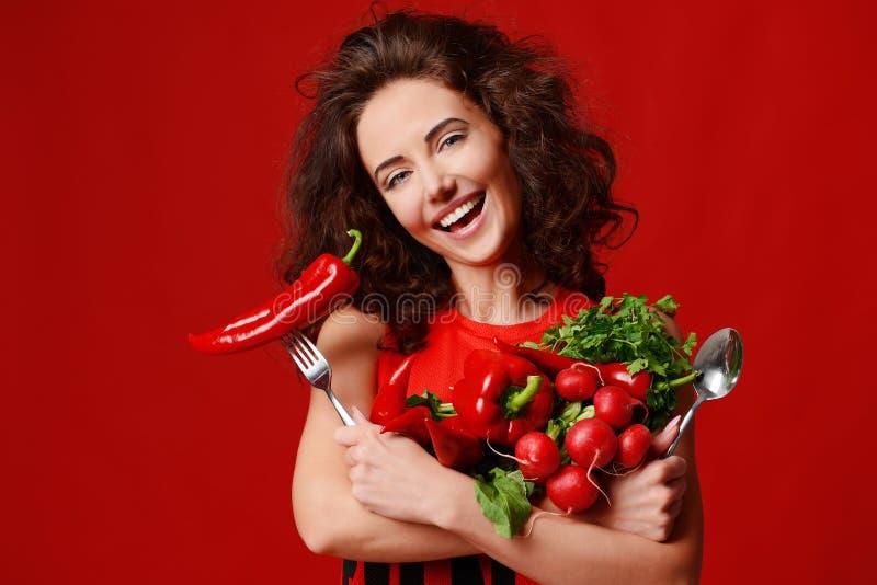 Милая молодая женщина представляя с свежими красными вилкой и ложкой петрушки салата листьев зеленого цвета перца chili редиски о стоковое изображение