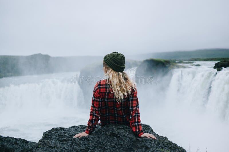 Милая молодая женщина сидит на крае скалы Исландии стоковое фото rf