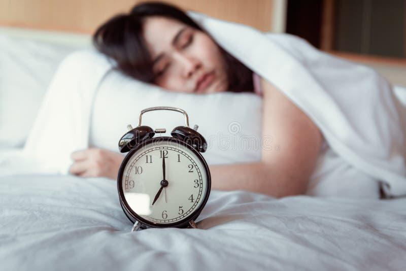 Милая молодая женщина спит и будильник в спальне, красивая девушка спит на ее кровати и ослабляет в утре , стоковые изображения rf
