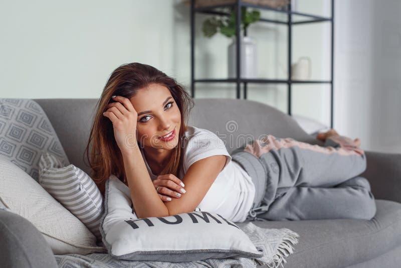 Милая молодая женщина с красивыми лож улыбки на сером кресле с подушками на уютном доме Милая девушка имея остатки дома внутри стоковая фотография rf