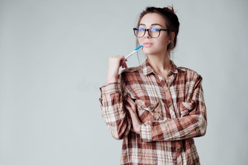 Милая молодая ручка удерживания девушки брюнета и обдумывать, выглядя внимательный стоковое фото rf