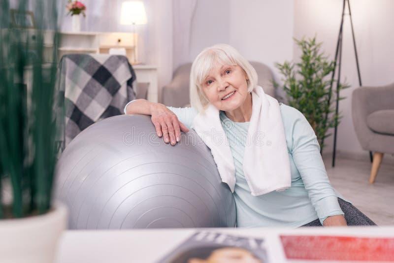 Милая пожилая склонность женщины на шарике и усмехаться йоги стоковые изображения rf