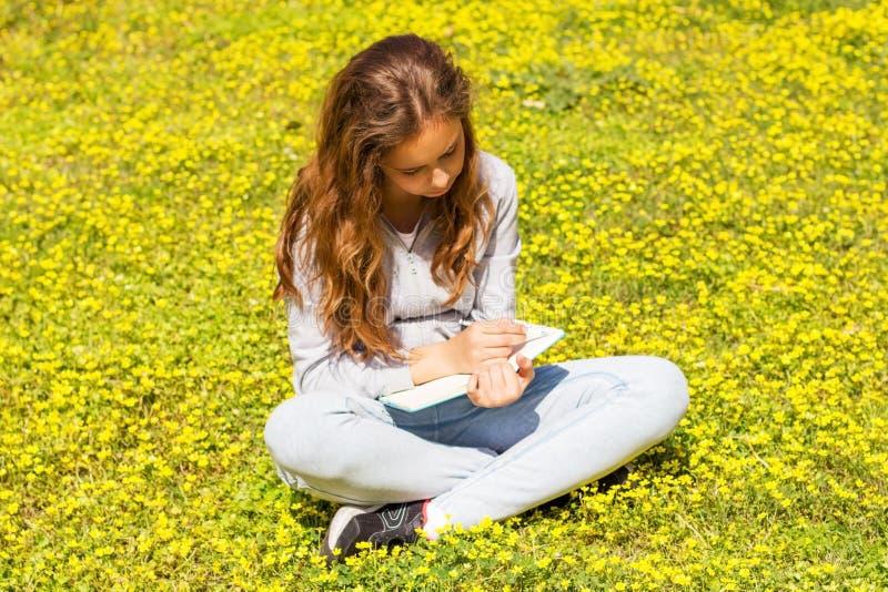 Милая предназначенная для подростков девушка пишет примечания на бумажной пусковой площадке на зеленом луге r стоковые изображения rf