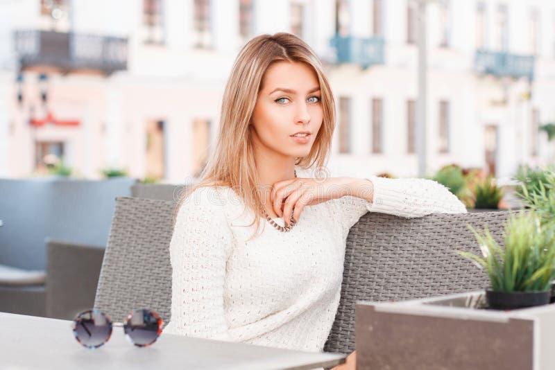 Милая привлекательная молодая женщина с голубыми глазами в стильном связанном свитере сидит на винтажной софе в на открытом возду стоковые фото