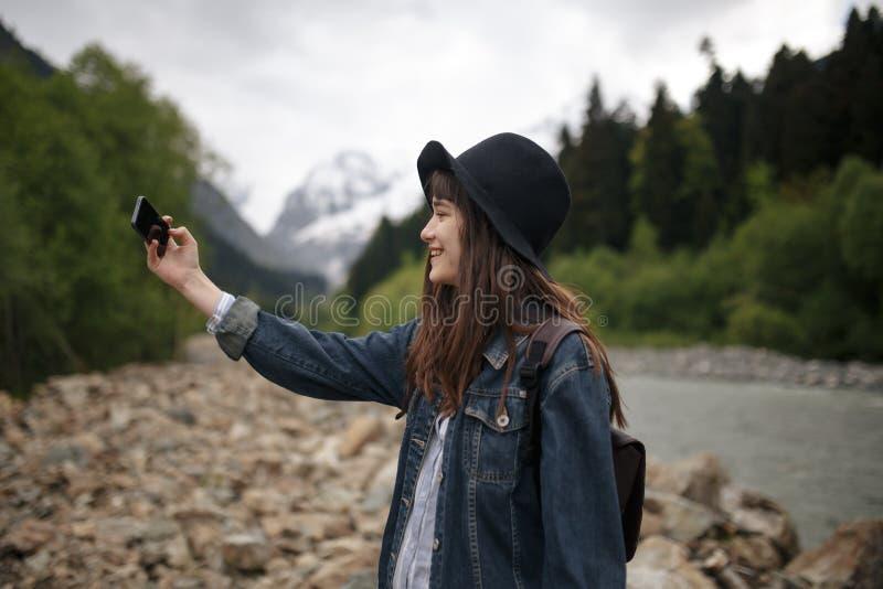 Милая путешествуя женщина стоя na górze горы на заходе солнца и используя мобильный телефон стоковое фото