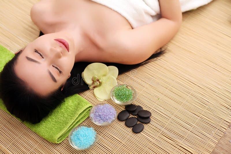 Милая расслабленная молодая женщина кладя в салон курорта с закрытыми глазами стоковые фото