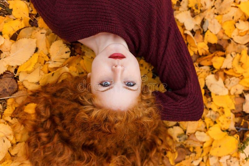 Милая рыжеволосая девушка лежа на желтых листьях стоковые фотографии rf