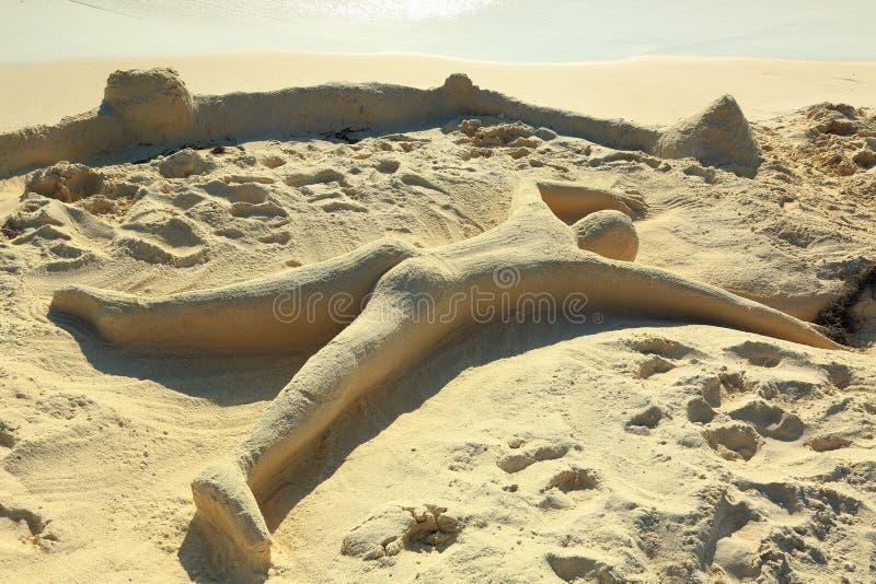 Милая скульптура песка представляя человеческий класть на пляж с стороной вниз Остров Аруба карибско стоковые фото