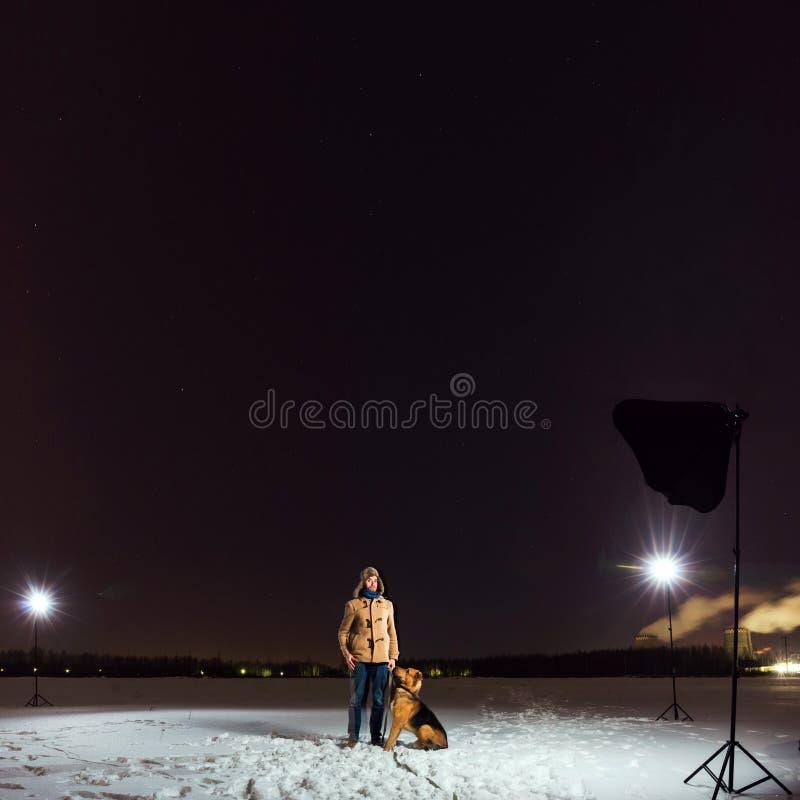 Милая смешанная собака породы с человеком сидя в поле вечером стоковое фото rf